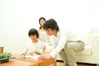 父親と雑誌を見る女の子と30代家族3人 22600004852| 写真素材・ストックフォト・画像・イラスト素材|アマナイメージズ