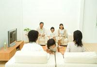 両親のソファに上る女の子と3世代家族6人
