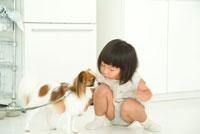 冷蔵庫の前でペットと戯れる女の子