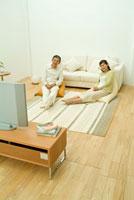 クッションに座りテレビ鑑賞するミドル夫婦