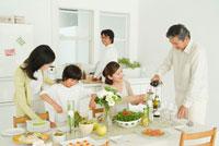 ワインを注ぐ祖父と食卓を囲む3世代家族5人