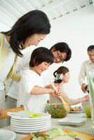 サラダを作る女の子と食卓を囲む3世代家族5人