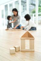 家の形をした積み木と床で遊ぶ母娘3人