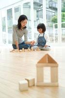家の形をした積み木と床で遊ぶ母娘2人