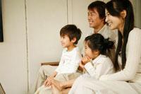 ソファに座りテレビを観る家族4人