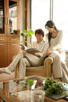 ソファにもたれて雑誌を読むカップル