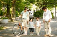 新緑の街を散歩する4人家族
