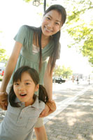 道で母親と戯れる女の子