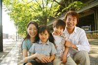 新緑の前で微笑む4人家族のポートレート