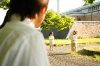 両親の前で公園の新芽を摘む兄妹