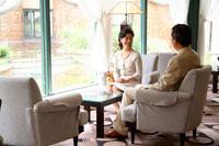 ホテルのソファで談笑するミドルカップル