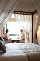 天蓋ベッドの部屋で談笑するミドルカップル 22600005114| 写真素材・ストックフォト・画像・イラスト素材|アマナイメージズ