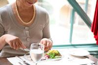 レストランで食事するミドル女性