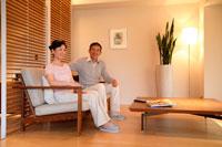 居間のソファでくつろぐミドルカップル