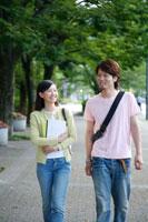新緑の道を歩く大学生カップル