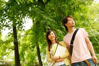 新緑の中を歩く大学生カップル