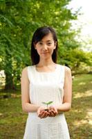 新緑の中で双葉を持った女性 22600005213| 写真素材・ストックフォト・画像・イラスト素材|アマナイメージズ