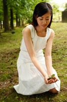 双葉を地面に還す20代女性 22600005216| 写真素材・ストックフォト・画像・イラスト素材|アマナイメージズ