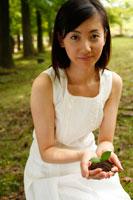 双葉を手に持ち微笑む20代女性 22600005217| 写真素材・ストックフォト・画像・イラスト素材|アマナイメージズ