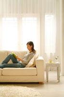 ソファで本を読みくつろぐ20代女性