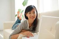 ソファでパソコンを楽しむ20代女性