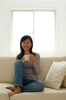 ソファでお茶を飲み微笑む20代女性