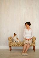 アンティークソファに子犬と座る20代女性