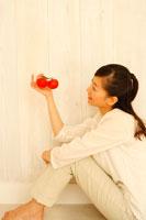 双子のトマトを座って見つめる20代女性 22600005276| 写真素材・ストックフォト・画像・イラスト素材|アマナイメージズ