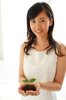 白い部屋で双葉を掌に微笑む20代女性 22600005289| 写真素材・ストックフォト・画像・イラスト素材|アマナイメージズ