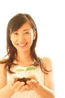 双葉を掌に微笑む20代女性 22600005291| 写真素材・ストックフォト・画像・イラスト素材|アマナイメージズ