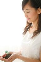 掌の双葉を見つめる20代女性 22600005293| 写真素材・ストックフォト・画像・イラスト素材|アマナイメージズ