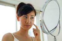 鏡を見ながら頬に指をあてる20代女性