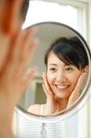 鏡を見ながら頬に手をあてる20代女性