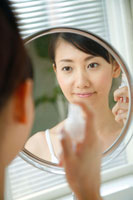 鏡を見ながら顔に霧吹きする20代女性