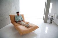 ソファで雑誌を見るミドル男性