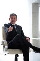 椅子に掛け指差すビジネスマン 22600005548| 写真素材・ストックフォト・画像・イラスト素材|アマナイメージズ