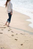 波打ち際を裸足で歩く後姿 20代女性