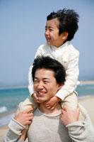 海岸で肩車をしている父と子