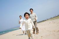 海岸を走る男の子と両親 22600005652A| 写真素材・ストックフォト・画像・イラスト素材|アマナイメージズ