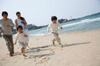 海岸を走る子供2人と両親 22600005655| 写真素材・ストックフォト・画像・イラスト素材|アマナイメージズ