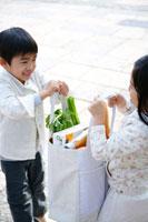 エコバッグを持ち上げる子供2人