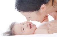 赤ちゃんに顔を近づけ微笑む母親