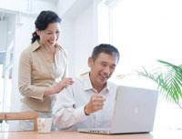 パソコンを見る笑顔のミドルカップル