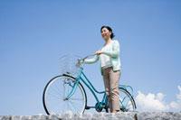 自転車を降り遠くを見つめるミドル女性