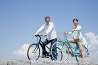 自転車に跨り微笑むミドル夫婦