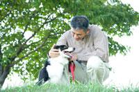 散歩道で犬を撫でるミドル男性
