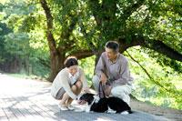 散歩道で犬を撫でるミドルカップル