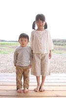 田園を背に立つ子供2人