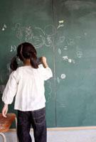 黒板に書き込む女の子