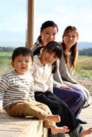ウッドデッキに座る2組の母親と子供 22600005827| 写真素材・ストックフォト・画像・イラスト素材|アマナイメージズ